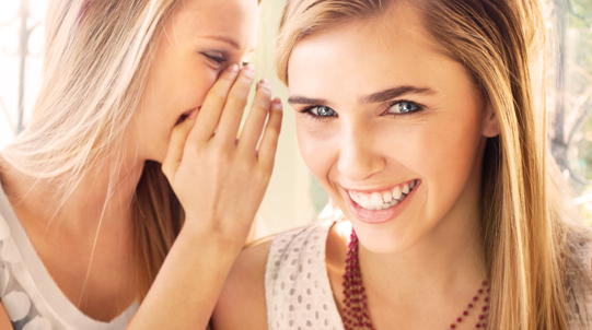 Woman smiles while her friend whispers in her ear