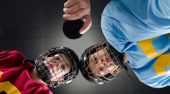 two boys playing hockey wearing mouth guards