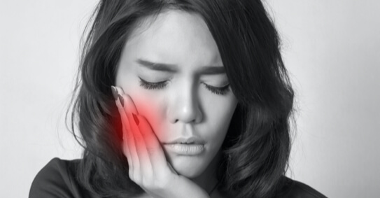 Black and white image of a woman holding her face with a red spot showing where she feels pain.