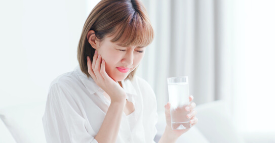 Asian woman holding a glass of water while feeling pain in her jaw.