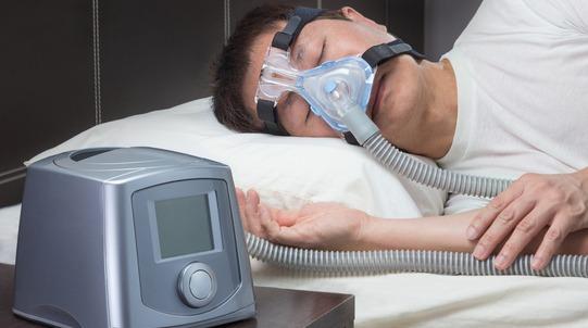 a man sleeping with a sleep apnea device